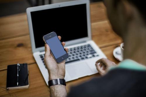 En hand som håller en mobil framför en dator
