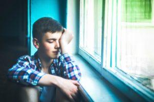 Pojke som sitter och blundar vid ett fönster
