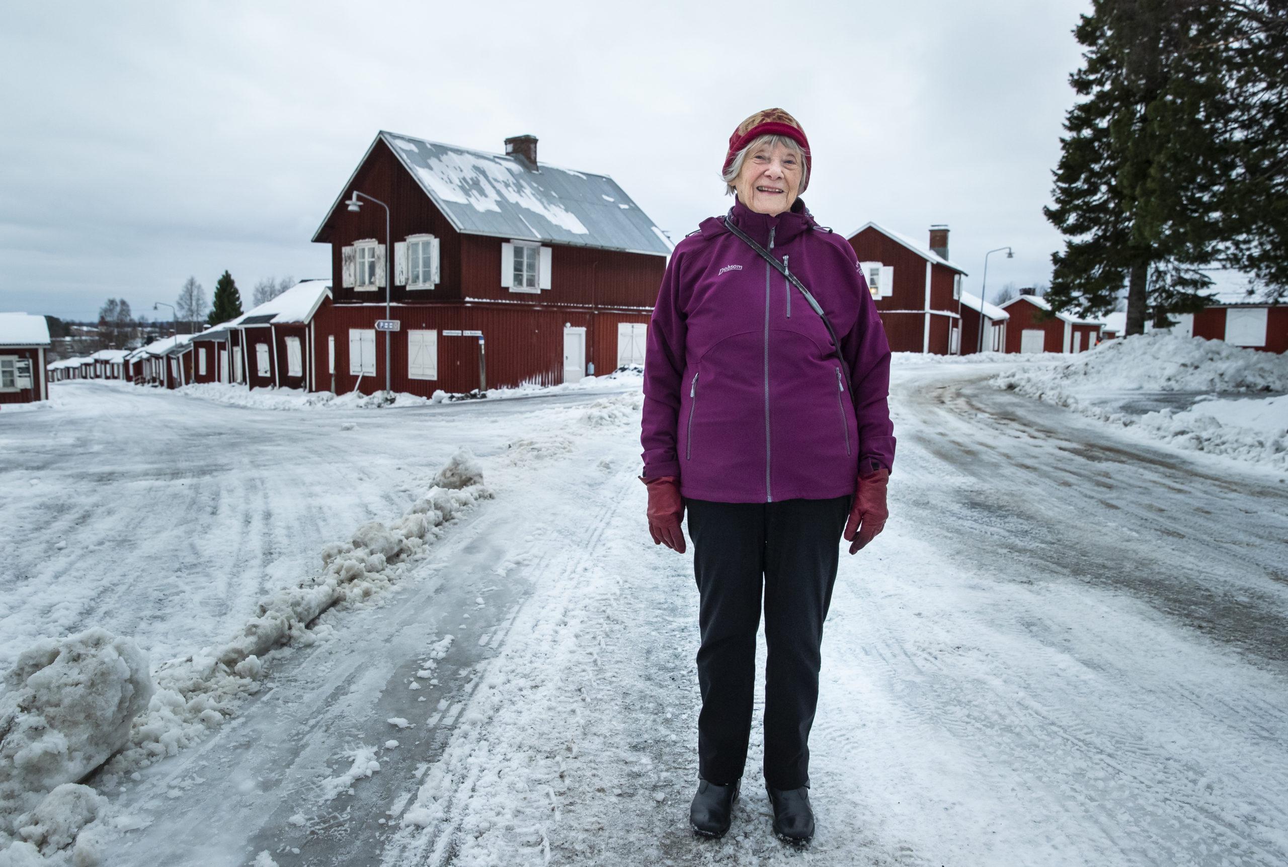 En kvinna står på en snöig väg.